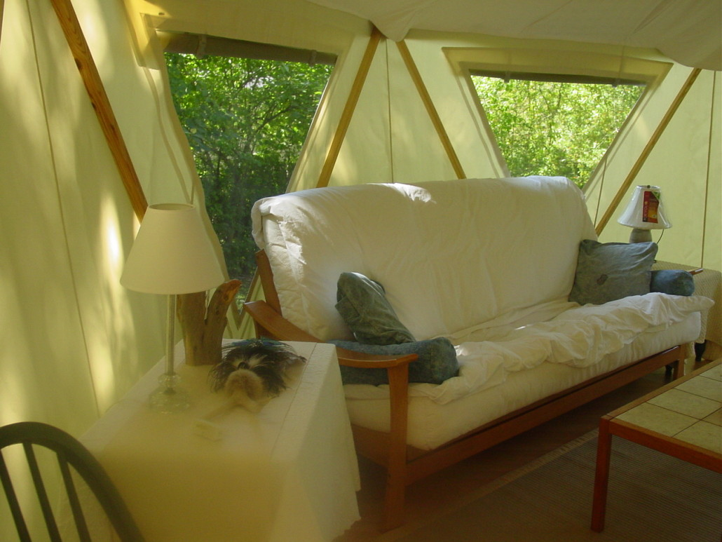 Bright light glowing interior of a Yome tent home with futon, tables and other furniture