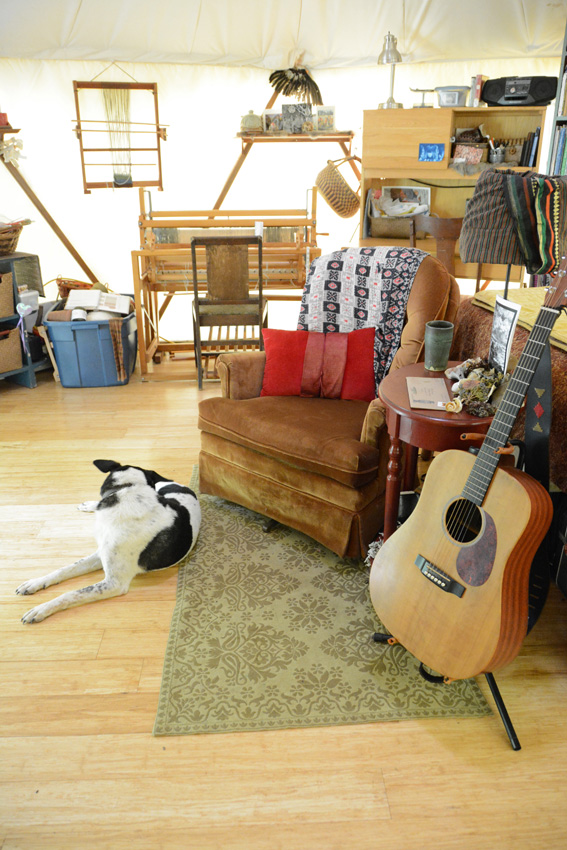 Happy dog, guitar and book shelves paint a cozy picture of the interior of this living tent home, a Yome by Red Sky Shelters