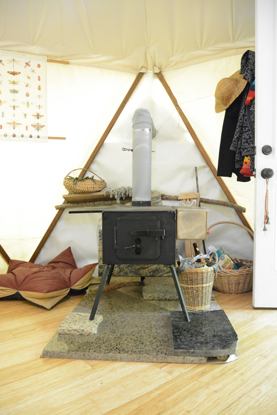 Wood stove placed on granit slab on hardwoods in a portable shelter tent home like a yurt but a Yome