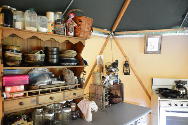 Knick knack cabinet with spice jars, handmade pottery, and cookbooks in a portable tent shelter called a Yome