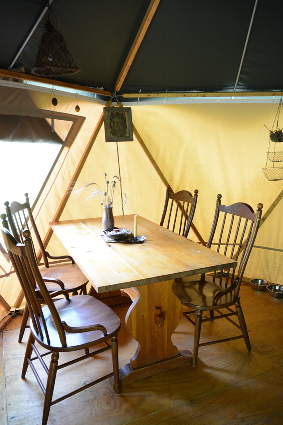 Kitchen table with flower vase and antique wood chairs in yurt-like Yome tent home