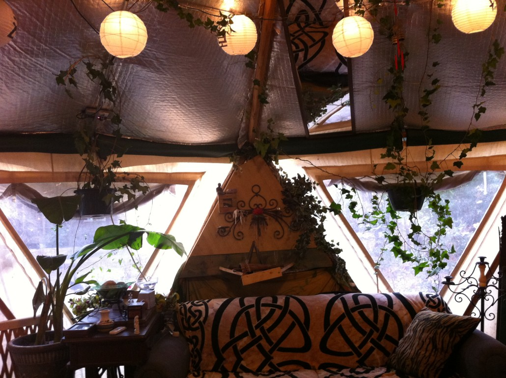 A beautifully decorated Yome tent home with lighting globes, plants and vines and comfy looking couch