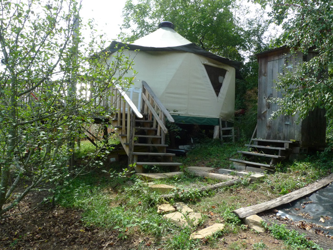 Outhouse, walking path, and Yome style yurt home with large deck at the edge of the forest