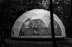 A geodesic dome installed in the woods with clear covering