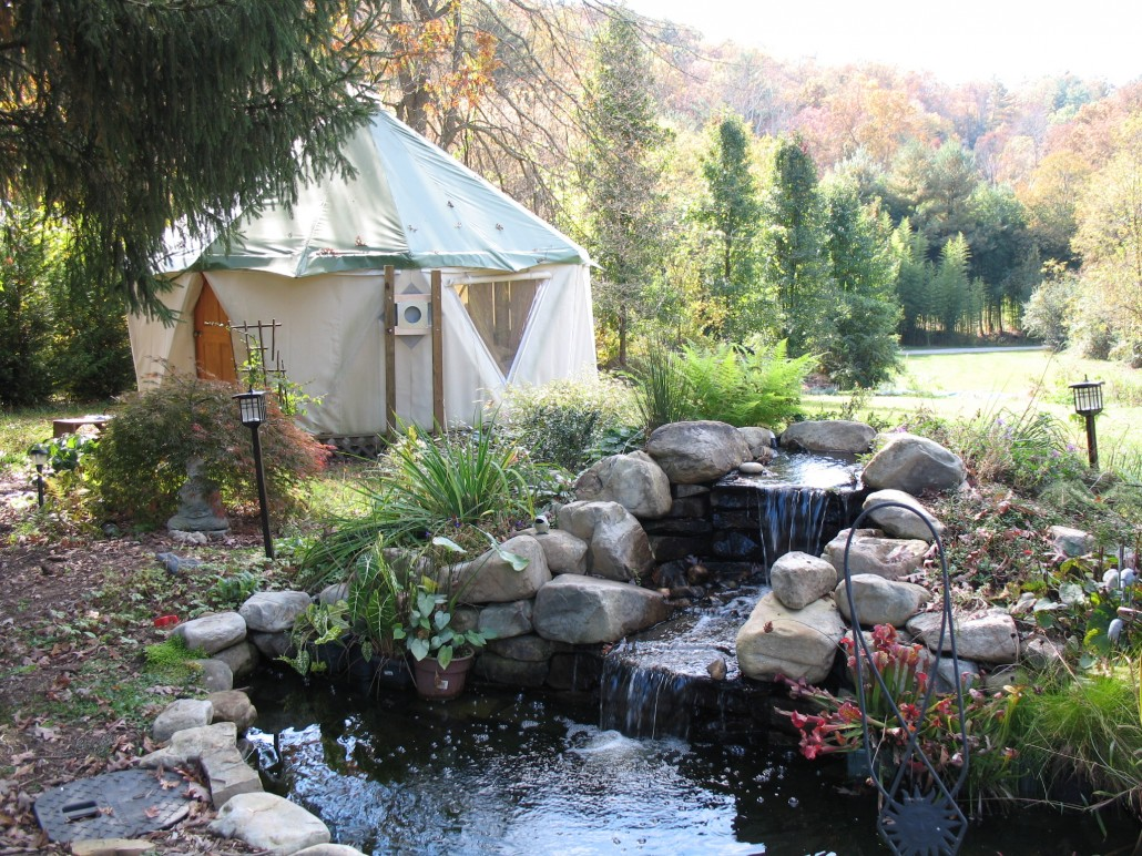 Yurt home aka Yome by Red Sky Shelters shown by beautiful water feature pond with waterfall and stones