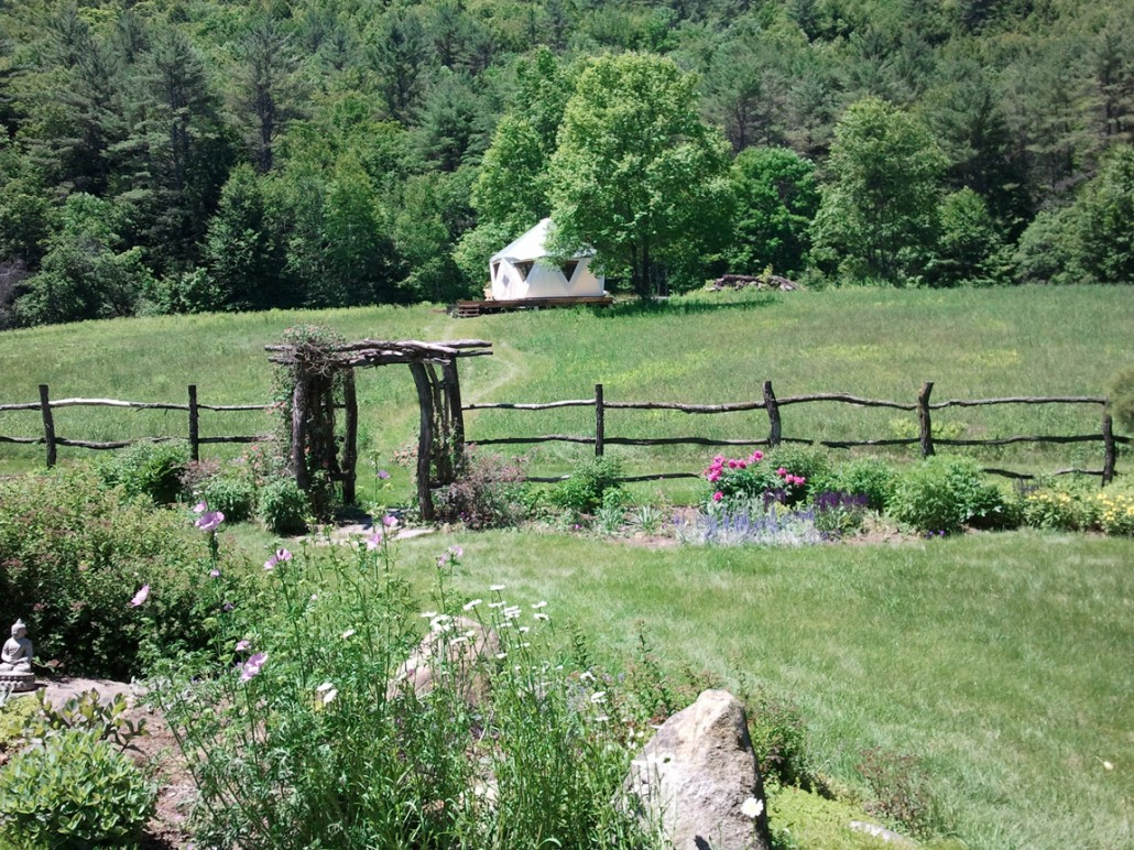Landscape photo of Yome tent yurt home in the distance in a pasture with wildflowers and natural wood arch and fence
