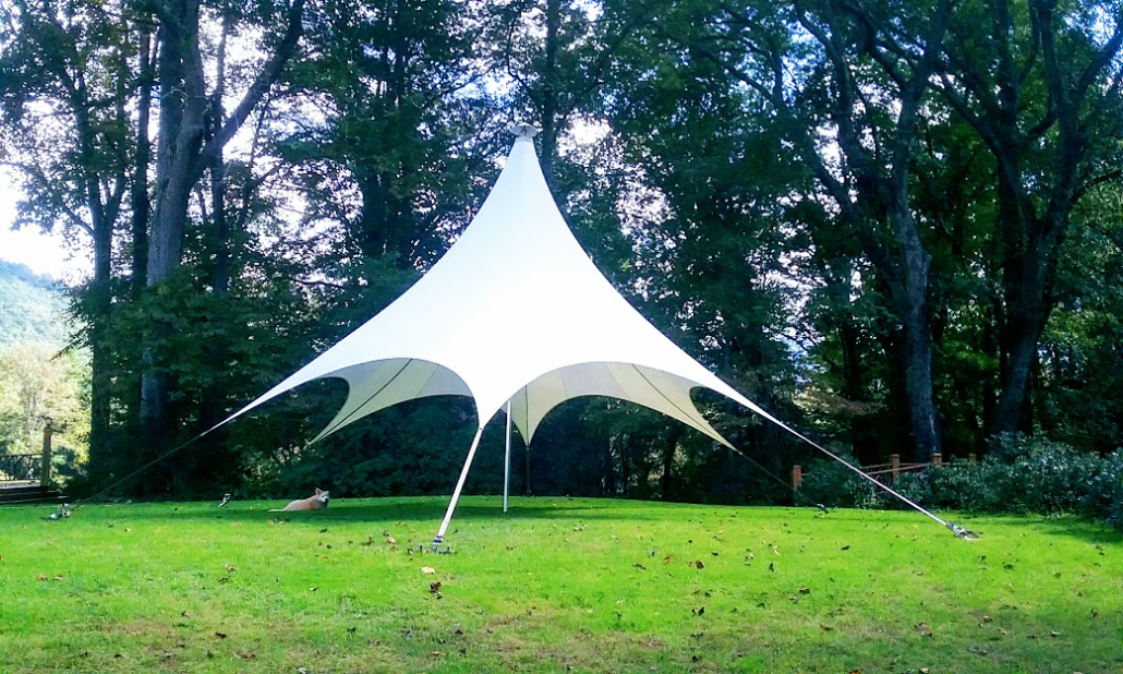 A large white shade tent on grassy lawn