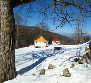 Brightly colored tent homes in the mountains stand out against the snow covered ground