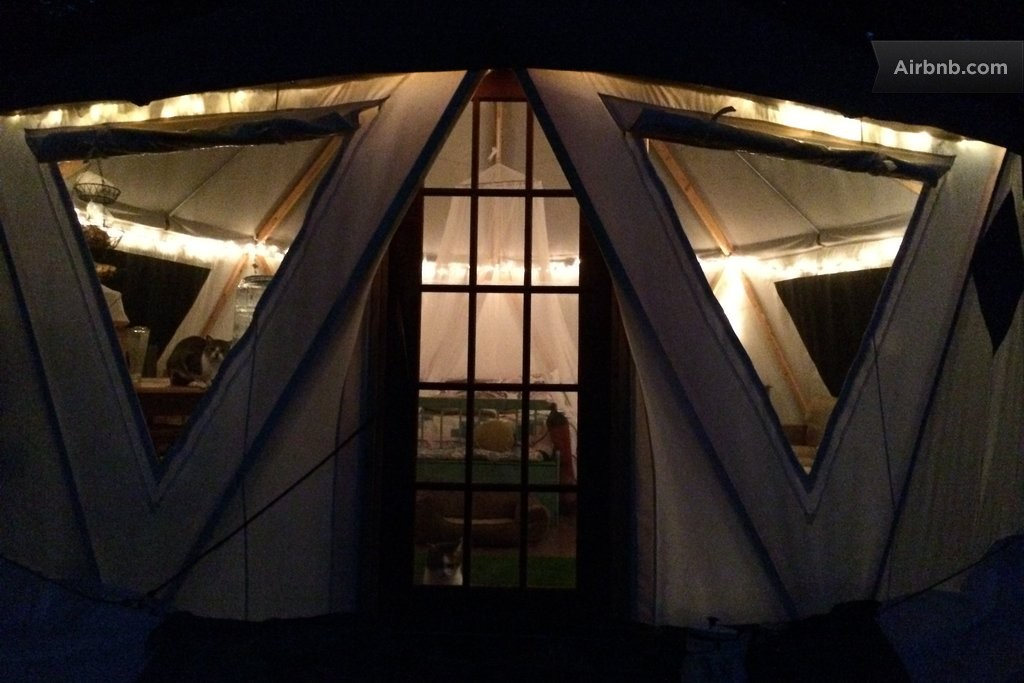 Beautifully illuminated Yome branded yurt home seen from outside at night through expansive windows