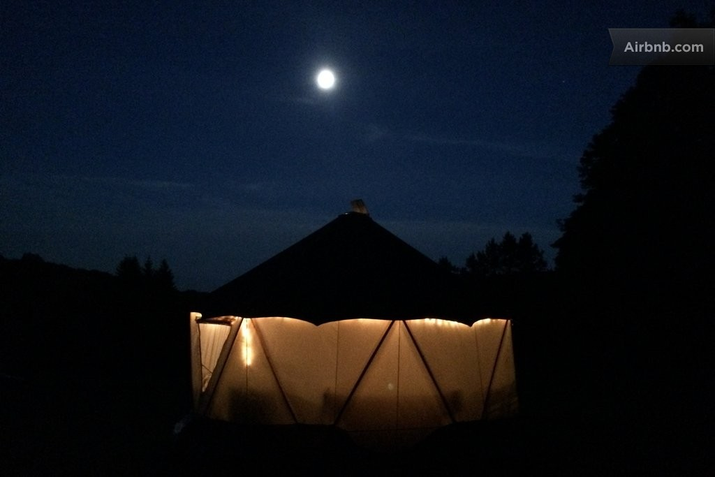 Glowing photo of nighttime Yome style yurt dwelling illuminated from within with large full moon in the distance