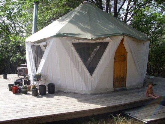Yurt like tent home on broad deck with small child and plantings