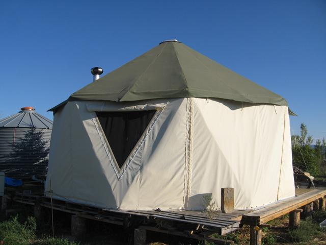 A group of portable shelter homes on wood decks including true yurts and the yurt-dome hybrid Yome by Red Sky Shelters