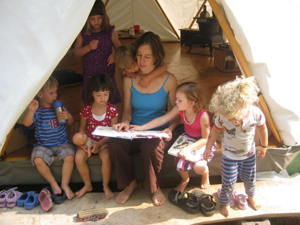 Woman teaching a group of small children in a portable tent home Yome like a yurt but stronger and more affordable