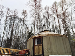 A yurt home in situ with wood stove and some wear to fabric