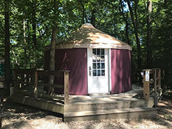 A yurt at a commercial campground installed with a wraparound wood deck